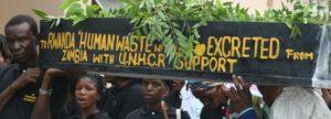 """Réfugiés portant un tombeau sur lequel est inscrit """" Excréments humains à expédier au Rwanda en provenance de Zambie avec le support du HCR"""""""